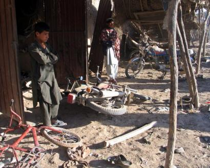 Afghan boys stood at the site of a suicide bombing in Lashkar Gah, Afghanistan, yesterday. Three civilians and a policeman were killed, the Interior Ministry said.