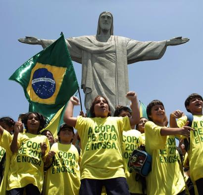 In front of the statue of Christ the Redeemer in Rio de Janeiro, fans celebrate the awarding of the 2014 World Cup to Brazil.