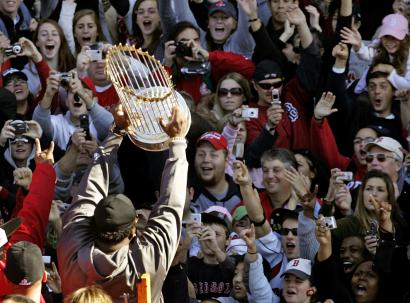Red Sox slugger David Ortiz hoisted the World Series trophy to fans on Tremont Street during yesterday's parade. The team's recent successes have been built on the signing of free agents such as Ortiz, judicious trades, and the grooming of young talent.
