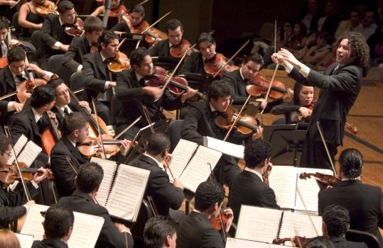 Venezuelan conductor Gustavo Dudamel (standing) and the Simón Bolívar Youth Orchestra are the most exciting thing in classical music.