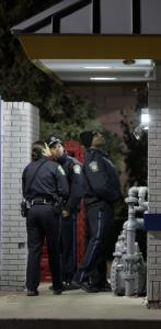 Boston police examined evidence near a parking lot where they said one person had been shot in the shoulder last night.