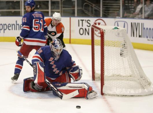 Goalie Henrik Lundqvist sweeps aside a first-period shot, one of 30 saves he made in the Rangers' 2-0 victory over the Flyers.