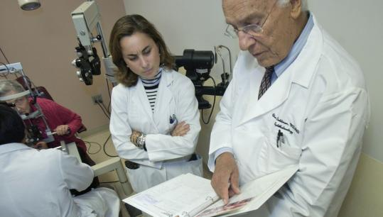 Dr. Claes Dohlman (right) looks over medical information with Dr. Ana Fernandez-Hortelano for patient Phyllis Blumsack (at left rear).