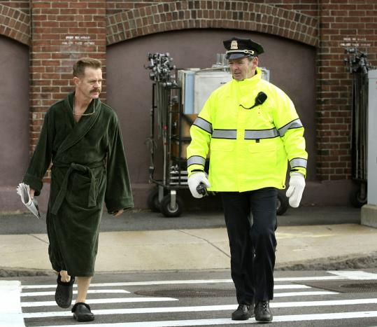 William H. Macy is escorted across Summer Street by Boston Police Sergeant Michael O'Connor yesterday.