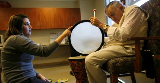 Coordinator Jessica Dupont of the New England Homes for the Deaf works with resident Nick Dadonna in a drumming class.