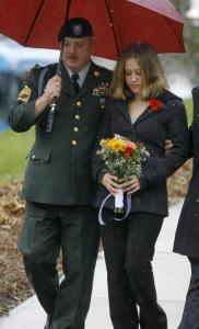 Michelle Muller, widow of Private Adam Muller, was escorted out of a memorial service by an unidentified soldier yesterday.