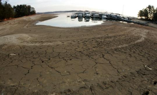 The exposed lake bed of Lake Lanier was visible at Aqualand Marina in Flowery Branch, Ga., last Sunday. A federal plan will allow a reduction in water flowing downstream from the drying lake.