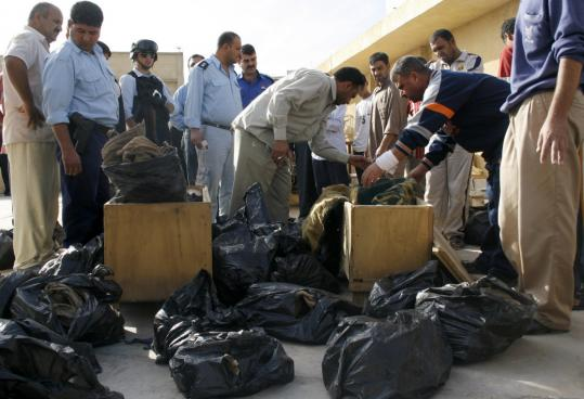 Iraqis examined human remains found in a mass grave in southern Baghdad yesterday. Relatives of people who had been missing crowded the area where the remains were shown.