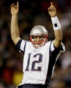 Tom Brady, shown celebrating his fifth touchdown pass, isn't about to apologize for his team's offensive approach.