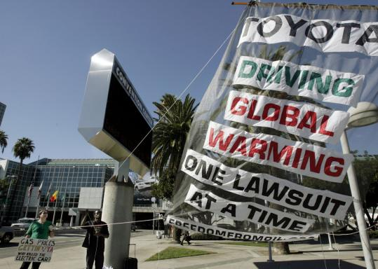 A protest against Toyota and global warming last week at the Los Angeles Auto Show. An MIT study says higher energy prices and new technologies will slow the growth of greenhouse gases.