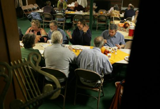 At a dinner in a church basement this month in Barre, Vt., support teams and former inmates, including Steve Gibson (gesturing), enjoyed a communal dinner.