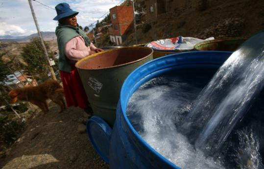A woman waited as water tanks were filled in the outskirts of La Paz recently. Scientists predict that all the glaciers in the tropical Andes will disappear by mid-century.