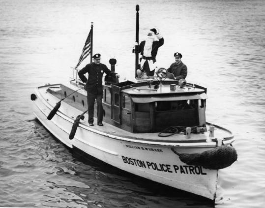 A 1956 photo shows Globe Santa making a happy landing thanks to the seamanship of Boston police harbor patrolmen William Kenneally and Anthony Scavongelli.