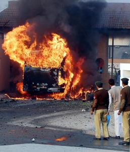 Security officials watched a Defense Ministry bus that became engulfed in flames yesterday after an attack in Rawalpindi.