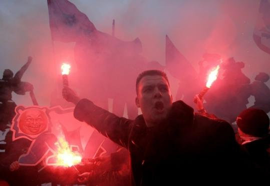 A left-wing demonstrator held a flare as others set fire to a caricature of Mayor Yuri Luzhkov at a protest in Moscow.