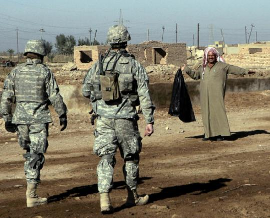 An Iraqi showed US soldiers yesterday in Baqubah that he had no weapon. In one attack in the city, a bomber killed six.