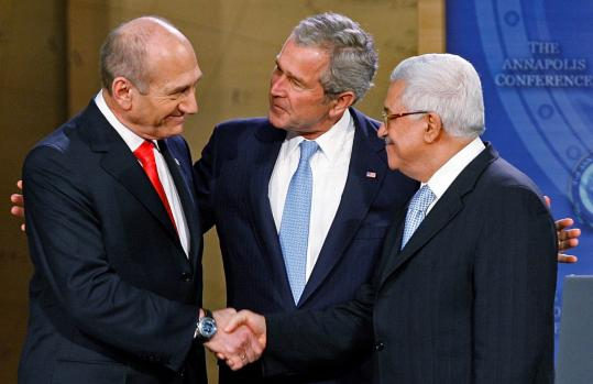 Israeli Prime Minister Ehud Olmert (left) shook hands with Palestinian President Mahmoud Abbas yesterday in Annapolis, Md.