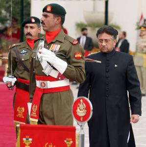 After taking the oath of office as a civilian president, Pervez Musharraf (right) reviewed an honor guard in Islamabad.