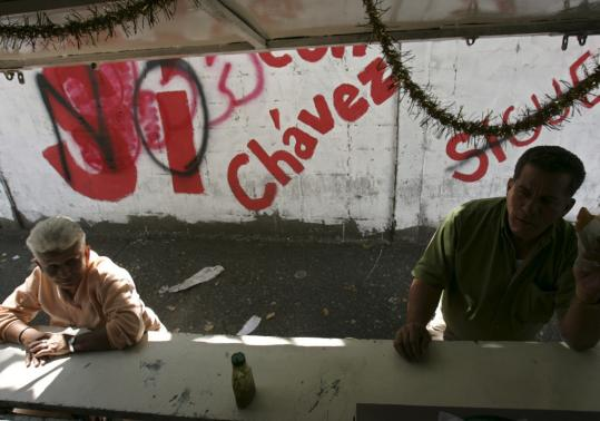 'Yes, with Chavez' and 'No' in reference to the referendum on changes to the constitution was painted across from a Caracas eatery where patrons waited for breakfast yesterday.