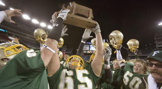 Bishop Feehan's Chris Paine (65) did some heavy lifting during and after the game - in the form of the championship trophy.
