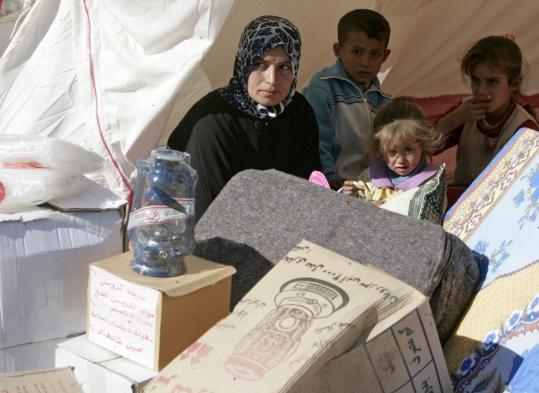 Refugees received aid from Red Crescent in a tent at a camp in Yusufiya, south of Baghdad on Monday. Hundreds of Iraqis have been displaced by the violent turmoil in Iraq.