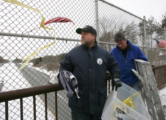 Ramon Jimenez (left), whose son was kidnapped in Iraq, and James Wareing complied with an order to remove flags from a Methuen bridge.