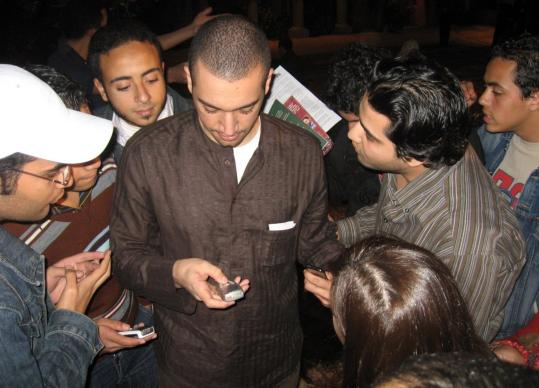 Young supporters crowded around Moez Masoud as he entered his number into their phones so they can send questions via text message. Masoud is one of a number of young Muslim preachers who are promoting an upbeat and tolerant brand of Islam.