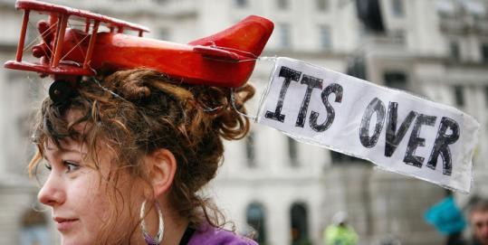 A climate protester in London wore a toy plane on her head. Rallies were held in more than 50 cities yesterday.