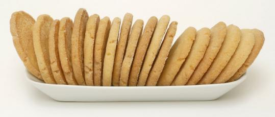 Sugar cookie dough is rolled into balls, dropped onto a dish of sugar, then flattened with a glass to make even discs.