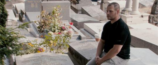 Embalmer David Pouly sits by Modigliani's grave at the Pere-Lachaise Cemetery in Paris.