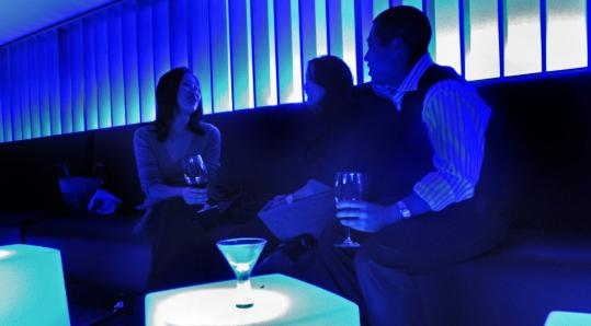 The walls and tables in the downstairs lounge, which sometimes serves as a second dining room, are illuminated by LED lights.