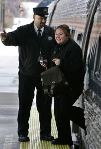 A conductor helped a passenger off the Amtrak Downeaster as the train arrived in Portland, Maine, yesterday. A request to the Maine Legislature for funding will not be a slam dunk because it occurs as the state grapples with a backlog of bridge and highway repairs.