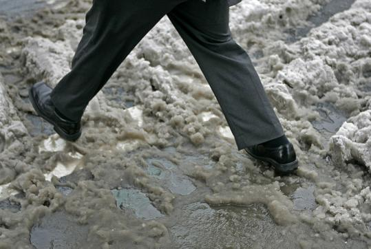 A pedestrian without boots walked through slush on Boylston Street yesterday. Forty-degree temperatures melted much of the snowfall.