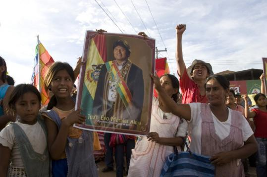 Supporters of Bolivia's president, Evo Morales, holding a poster of him, celebrated approval of a new constitution on Friday.