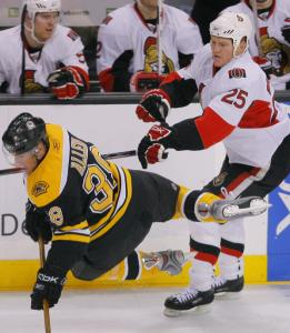 Bruin Bobby Allen is a hit with Chris Neil, who sends him flying in front of the Ottawa bench.