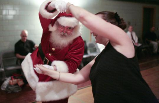 Jonathan Meath, dressed as Santa Claus, dances with Donna LaRue of Arlington at Swing City in Newton.