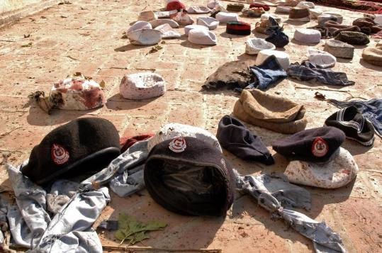 Caps of police and worshipers were scattered near a mosque yesterday after a suicide bombing in Pakistan near Afghanistan.