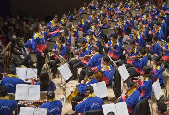 Gustavo Dudamel and the Simon Bolivar Youth Orchestra wore the colors of Venezuela's flag during encores at Symphony Hall.