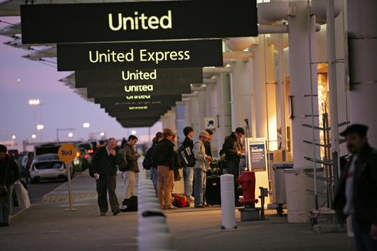 Travelers using the curbside check-in for United Air Lines and United Express during the early morning hours Christmas Eve at Denver International Airport. The airline says it has been hit hard by this week's storms in the Midwest.