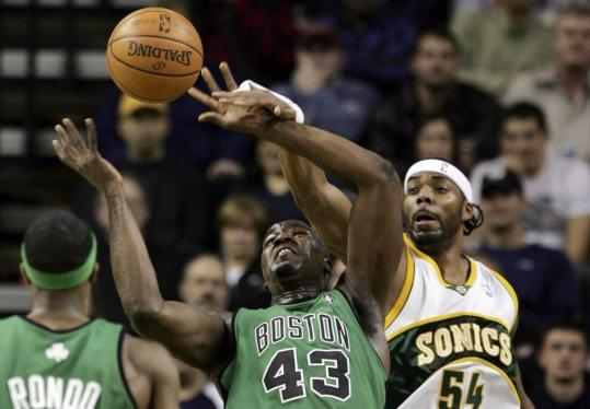 The Celtics' Kendrick Perkins battles Seattle's Chris Wilcox for possession of the ball.