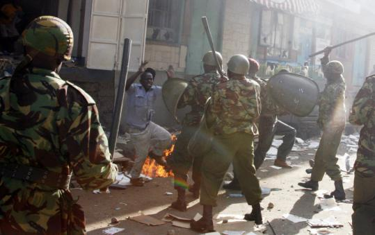 A looter was confronted by Kenyan riot police after he was kicked out of a store he was ransacking in the Mathare neighborhood of Nairobi yesterday. With votes in 180 of 210 constituencies counted, opposition leader Raila Odinga clung to a small lead over incumbent Mwai Kibaki by 38,000 votes, but delays in the tallying raised suspicions of rigging and sparked nationwide riots.
