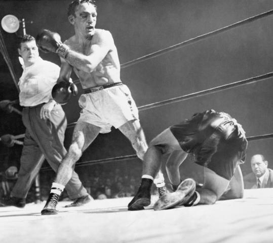 Tony DeMarco slumps to the canvas below Carmen Basilio in a fight at Boston Garden in December 1955.