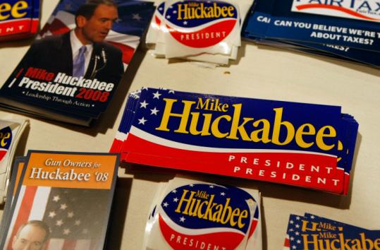 The merits of the consumption tax are being debated, with Mike Huckabee, a backer, contending for the GOP nomination,