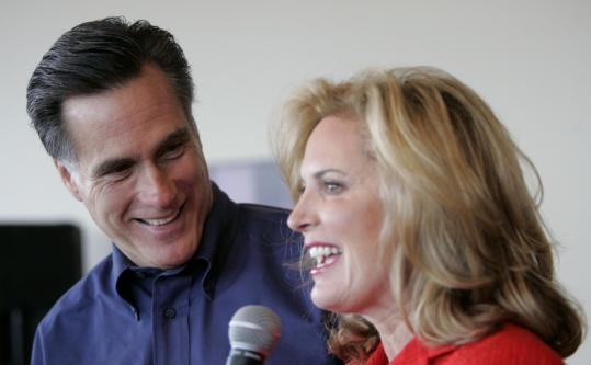 Mitt Romney with his wife, Ann, Saturday in Altoona, Iowa. Romney said he was unsure of the amount he had put into his campaign during the past three months.