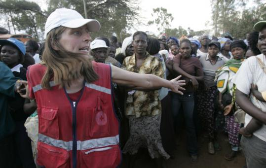 A Red Cross volunteer tried to keep Kibera residents back as they lined up yesterday to receive food aid in Nairobi.