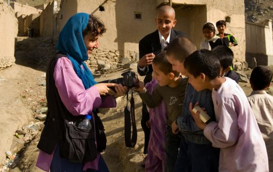 Belmont photojournalist Paula Lerner shows her digital camera to children playing in Kabul, Afghanistan.