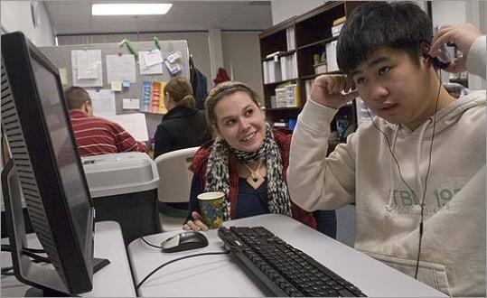 Teacher Mackenzie Marcet works with Robert Le in a narrow space at a Nashoba Learning Group facility for autistic students in Westford.