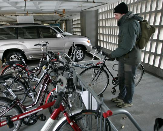 Mark Moreau, cofounder of a bike-borrowing program at Cambridge Innovation Center, puts a set of wheels in the rack. 'We're doing this,' he says, 'as a service to our clients.'