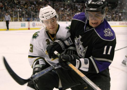 The Kings' Anze Kopitar, who scored a second-period goal, battles along the boards with Dallas's Stephane Robidas.