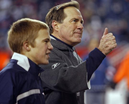 Bill Belichick signals thumbs up to the cheering crowd as he and one of his sons leave the field after last night's win.